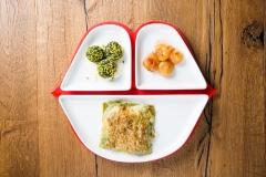 Fai felice la nonna - Lasagnette verdi al ragù di carni bianche, besciamella senza burro, cipolline agrodolci e polpettine di spinaci in grandella di pistacchi